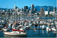 This photograph shows small boats in a marina with downtown Vancouver in the background.